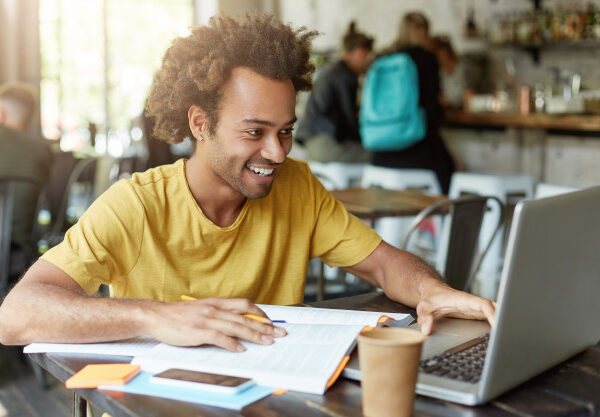 indoor-shot-happy-student-male-with-curly-hair-dressed-casually-sitting-cafeteria-working-with-modern-technologies-while-studying-looking-with-smile-notebook-receiving-message-from-friend_273609-7468